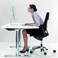 Verkrampfte Sitzhaltung beim Sehen mit einer Lesebrille vor dem Bildschirm
